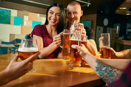 Front view of cheerful pair sitting at table in bar and laughing with friends while drinking beer. Young people resting on weekends with company in pub. Concept of free time and happiness. Stock fotó