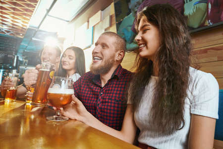 Side view of cheerful friends laughing and joking while drinking ale in pub. Happy men and woman sitting together in bar and toasting on weekends. Concept of happiness and fun. Stock fotó
