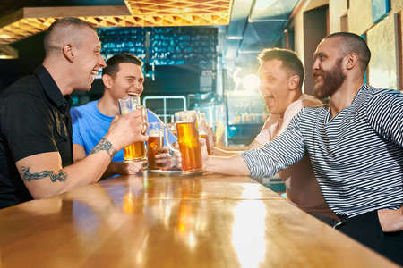 Side view of happy male company enjoying evening in pub. Four strong men joking, talking and laughing at each other while drinking tasty beer in bar. Concept of beverage and fun.