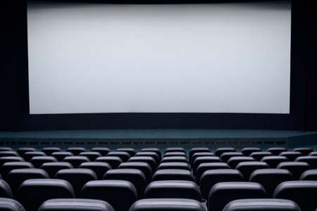 Interior cinema hall with white screen and black comfortable chairs. Concept of empty cinema hall. Stock fotó