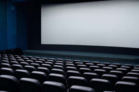 Cinema auditorium with black seats and white blank screen. Concept of cinema time. Stock fotó