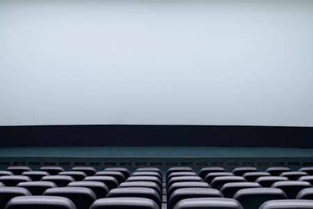 Close up of large blank screen and rows comfortable black seats for visitors in cinema hall. Concept of empty movie theatre. Stock fotó