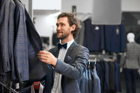 Close up of young man with curly hair choosing new jacket in store. Concept of shopping. Stock fotó