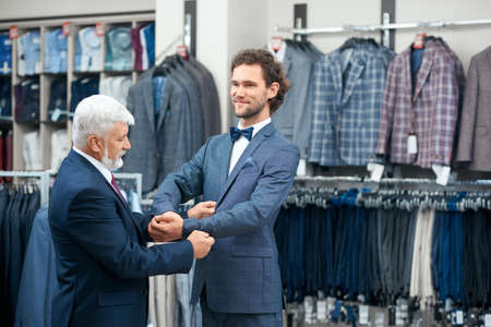Two elegant men coming fashion boutique on shopping. Concept of fitting fashionable costumes.