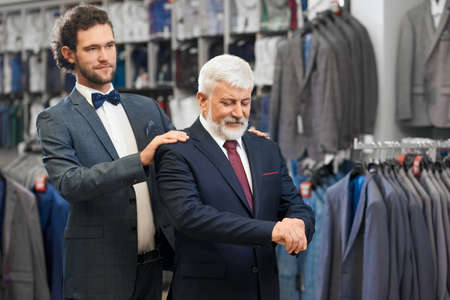 Close up of old elegant man in blue costume with tie and white shirt fitting fashionable costumes. Concept of senior man choosing costumes with young friend. Stock fotó