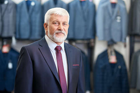 Portrait of senior man with grey beard and hair standing in store clothes for men. Concept of shopping.