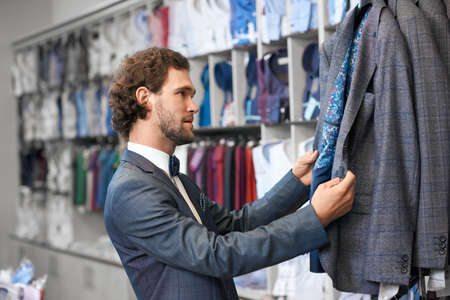 Young man with curly hair choosing stylish costumes in special store for man. Concept of process purchase.