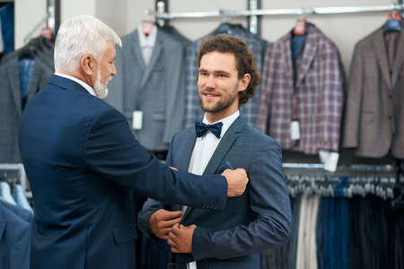 Two elegant men coming fashion boutique on shopping. Concept of picking up fashionable costumes. Stock fotó