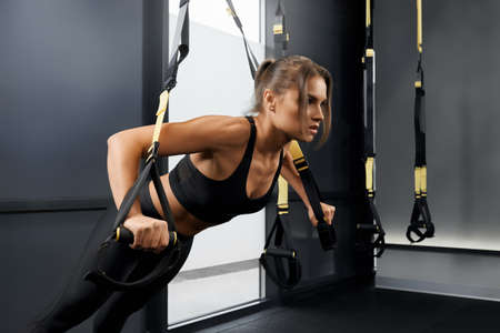Side view of young woman doing workout exercise with trx system. Concept of training with fitness straps in modern gym.