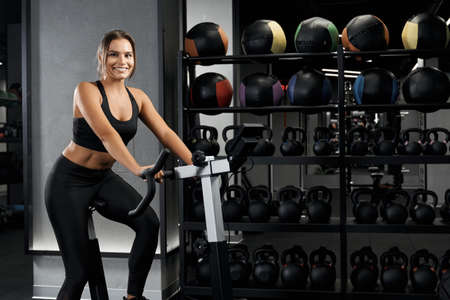 Smiling beautiful young woman in black sportswear engaged on exercise bike. Concept of active lifestyle and pump up body. Standard-Bild