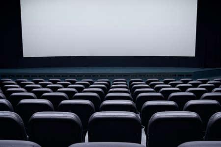 Cinema auditorium with black seats and white blank screen. Concept of interior cinema hall. Archivio Fotografico