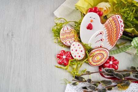 Easter composition of colored gingerbread, eggs, willow branches, flowers and lace doily over light wooden background. Concept of bright spring and happy holidays