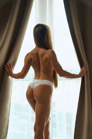 Back view of sensual woman posing near window, holding blinds, warm sun rays. Unrecognizable female model with athletic muscular body wearing white lace thong pants enjoying morning. Imagens