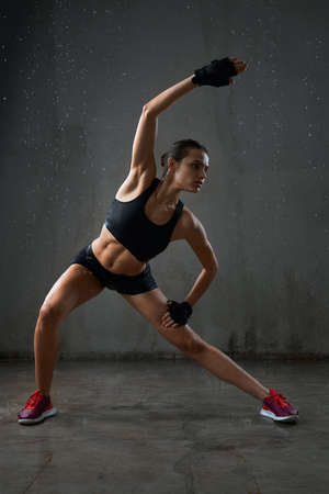 Fit female model practicing side body incline in side squat pose before training, isolated on loft gray studio background. Portrait of wet muscular fitnesswoman posing in sports underwear under rain.