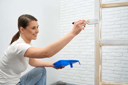 Side view of smiling brunette woman painting wooden rack in white color at home. Concept of improvement wooden rack.