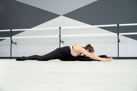Side view of flexible attractive woman stretching on floor. Adult female athlete putting face on knee, practicing split before competition in dance hall. Concept of gymnastics, healthy lifestyle.