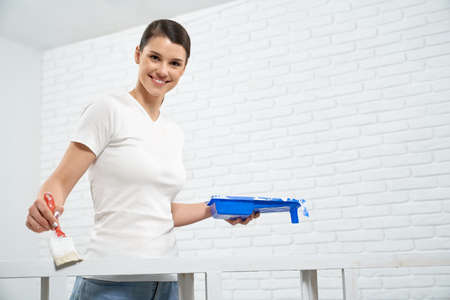 Smiling brunette woman painting rack in white color in empty room. Concept of repair at home.