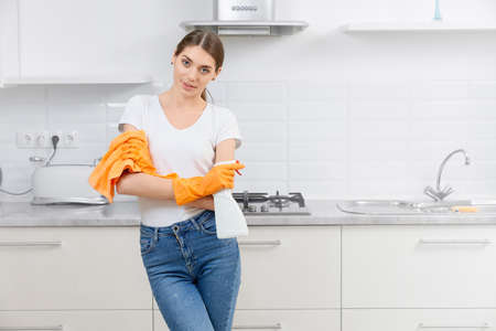 Young woman standing in modern kitchen with rag and detergent. Concept of preparing for cleaning kitchen. 版權商用圖片