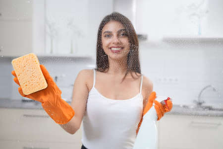 Close up of smiling young woman holding detergent and washing window in rubber gloves. Concept of chores.
