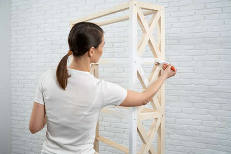 Close up of brunette woman holding brush and painting small wooden rack in white color. Concept of repair at home.