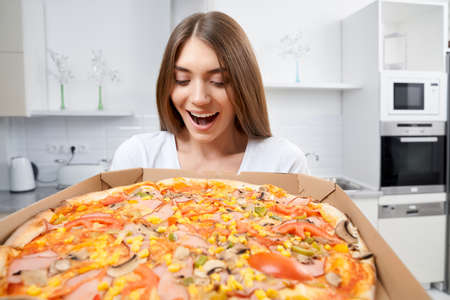 Happy young woman holding hot pizza in box at home. Concept of dinner in kitchen.