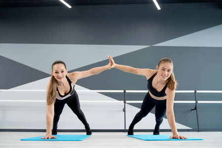 Front view of two stunning fitnesswomen practicing plank position and clapping hands on floor. Smiling attractive fit female dancers training on mats in ballet dance studio. Concept of sport. 版權商用圖片