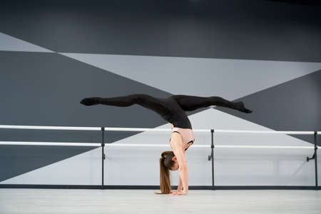 Side view of strong fit woman wearing sportswear standing on arms and practicing split in air. Flexible female dancer training before competition in dance hall with ballet handrails, hi tech interior.