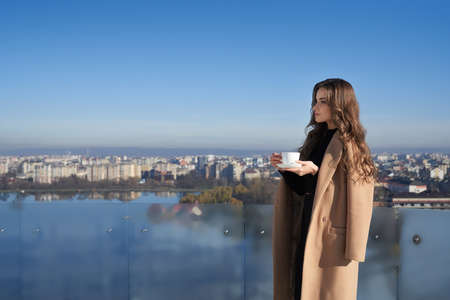 Side view of adorable young woman standing on balcony with cup of coffee and enjoying amazing view on big city. Concept of morning time and lifestyle. 版權商用圖片