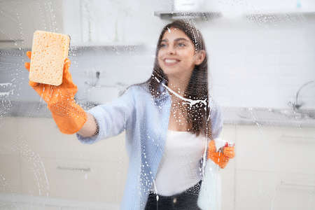 Smiling brunette woman washing window in rubber gloves with rag and detergent. Concept of cleaning window or glass. 版權商用圖片 - 168150460