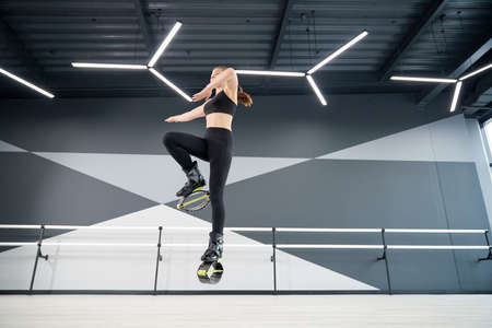 From below view of active female teenager doing cardio workout in hall, hi tech interior. Young pretty girl wearing black sportswear practicing dance moves while doing jumps and smiling.