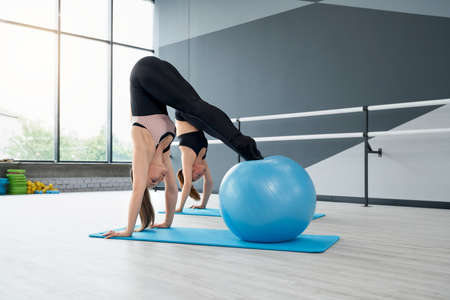 Side view of two attractive fit women training abdominal muscles, using big blue fitness balls in studio with handrails. Gorgeous fitnesswomen training abs on mats. Concept of sport.