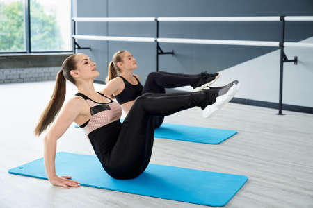 Adult instructor and female teenager training abs, sitting on mats in ballet dance studio with handrails. Gorgeous fitnesswomen building abdominal muscles on floor. Concept of healthy lifestyle. 版權商用圖片