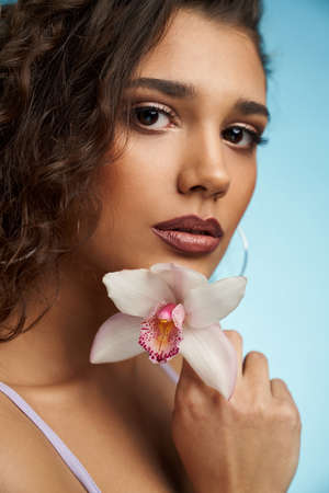 Portrait of attractive model with trendy makeup and curly hair holding beautiful white orchid on blue background. Concept of sensual and tender photo shoot on studio.