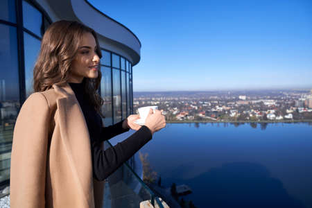 Gorgeous dark-haired woman enjoying beautiful view from high balcony of modern apartment. Beautiful lady enjoying morning time with cup of coffee. 版權商用圖片 - 168150476