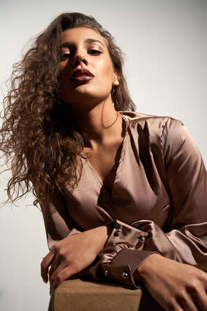 Fashion portrait beautiful brunette woman with curly hair in stylish in brown satin dress. Concept of model posing in trendy accessories and clothing in professional studio. 版權商用圖片