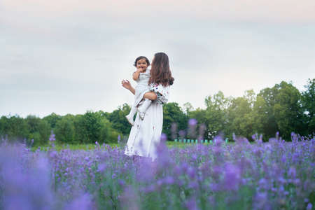 Young woman posing with baby girl on hands in summer lavender field. Side view of mother wearing dress carrying little laughing lovely kid. Concept of nature beauty, family.