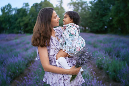 Side view of young loving woman posing with baby girl on hands in summer lavender field. Happy smiling mother wearing dress carrying beautiful bouquet of purple flowers. Concept of nature beauty.