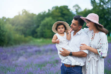 Happy family young couple posing with kid in lavender field. Little baby girl wearing straw hat sitting on hands of loving dad, looking at camera outdoors, aromatic flowers. Family, nature concept.