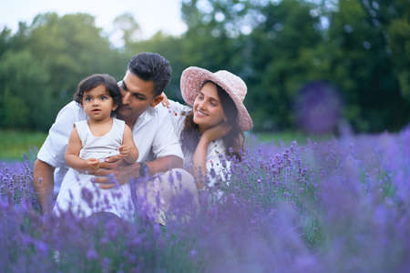Front view of mother, father and daughter sitting in lavender field and smiling. Cute baby girl, carrying flower and enjoying time with loving parents outdoors. Young family, nature concept.