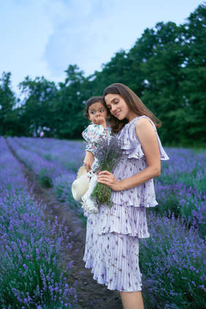 Side view of woman posing with baby girl on hands in beautiful summer lavender field. Young mother wearing dress carrying aromatic bouquet of purple flowers. Concept of nature beauty. 版權商用圖片