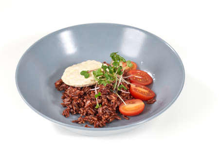 Close up of blue large plate with brown rice, tomatoes, greens and diet bread. Concept of delicious food with good composition and healthy food for emaciation or support body.