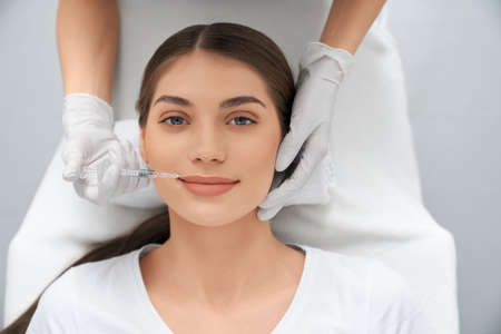 Top view portrait of smiling attractive woman lying in beautician and doing injection in lip with special preparation. Concept of process procedure lip augmentation in professional salon. Imagens