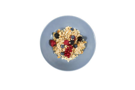 Top view of appetizing oatmeal with fresh berries and nuts in beautiful blue plate on white background. Concept of tasty porridge to support the figure or for emaciation.