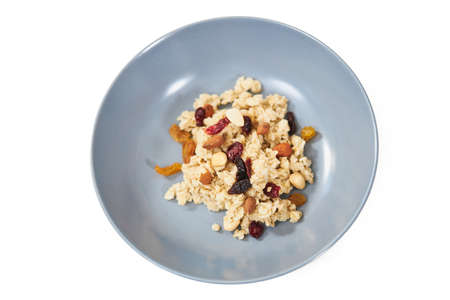 Top view close up of oatmeal with dried fruits and raisins in blue plate on white background. Concept of breakfast with appetizing porridge to support the figure.