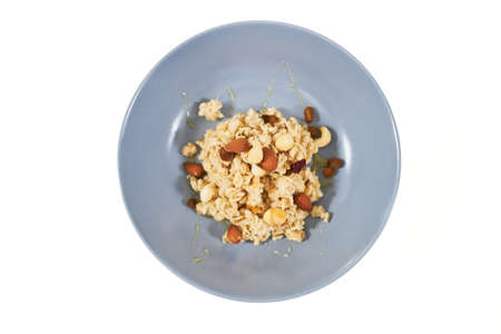 Top view of tasty and appetizing oatmeal with dried fruits and raisins,nuts on white background. Concept of delicious and healthy porridge for maintain body weight or emaciation.