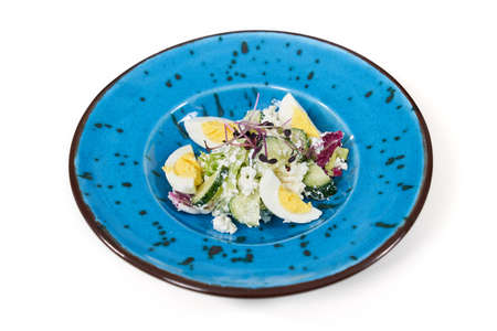 Close up of beautiful modern blue plate with delicious salad with vegetables and eggs on white background. Concept of appetizing salad with healthy vitamins for emaciation.