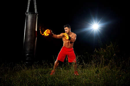 sportsman is training on the black night background, muscular body, boxing gloves in the fire, the night training training in open space on grass, boxing kick from the right hand, black punching bag