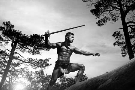 Power in every move. Low angle monochrome shot of a stunning masculine young warrior with a muscular body holding a sword climbing a rock copyspace 版權商用圖片