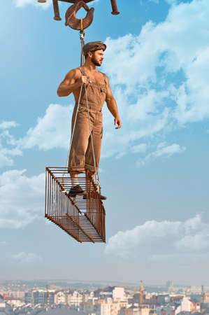 Gonna build this up. Vertical shot of a muscular old fashioned construction worker posing on a metal crossbar blue skies on the background 版權商用圖片