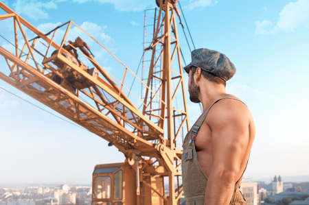 Human strength. Low angle shot of a strong muscular builder looking at the crane on a construction